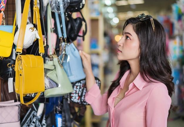 Bolso que elige y que compra de la mujer en tienda