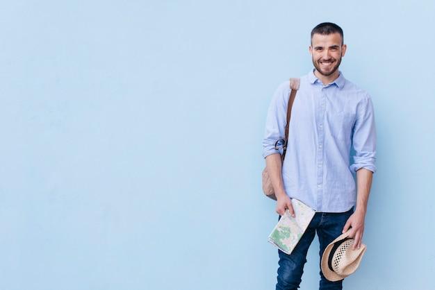 Bolso que lleva del hombre con sostener el mapa y el sombrero contra la pared azul del fondo