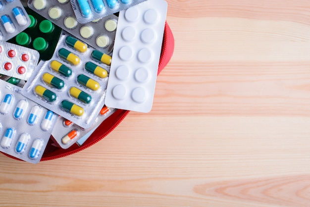 Bolso rojo con muchas pastillas diferentes contra la mesa de madera