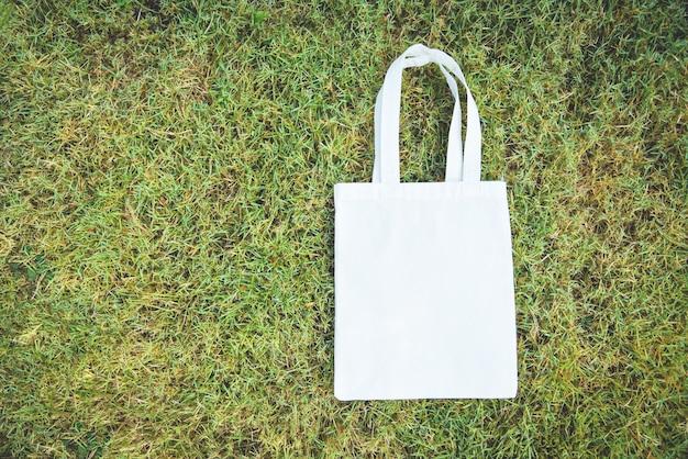 Bolso de tela ecológico de tela blanca en tela de lona bolsa de compras sobre fondo de hierba verde / cero desperdicio use menos plástico, digamos que no hay problema de contaminación de la bolsa de plástico