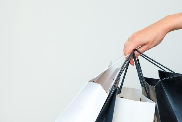 Los bolsos de compras blancos y negros del asimiento de la mano de la mujer en fondo gris claro.
