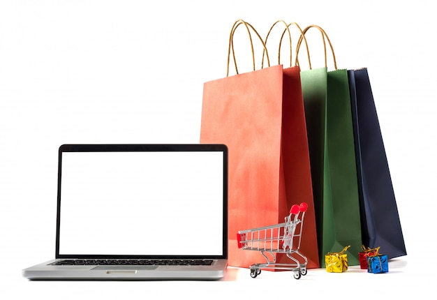 Bolsos de compras de papel coloridos, computadora portátil con la pantalla en blanco en el fondo blanco