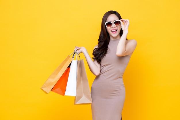 Bolsos de compras que llevan de la mujer asiática hermosa feliz en fondo  amarillo colorido 683375bc8173