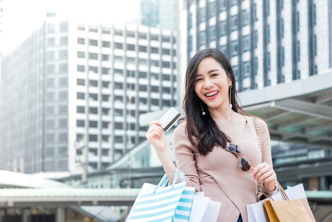 Bolsos de compras sonrientes de la mujer asiática que llevan y mostrando la tarjeta de crédito
