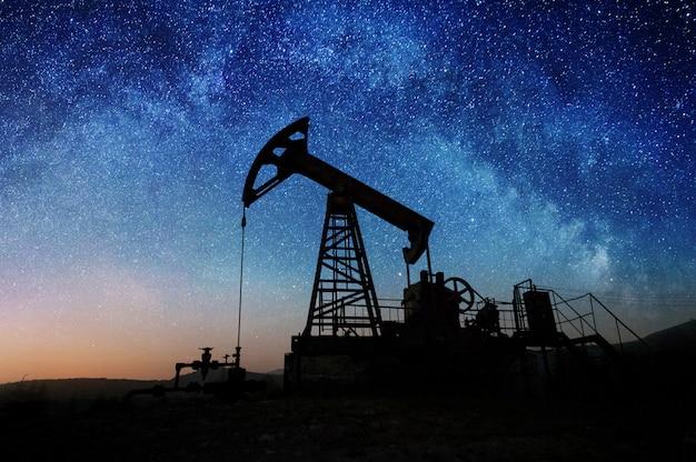 Bomba de aceite en el campo petrolero en la noche.