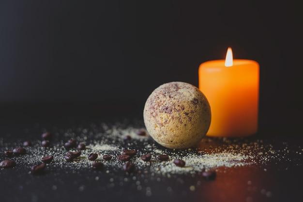 Bomba de baño y granos de café y velas encendidas sobre un fondo oscuro concepto de spa