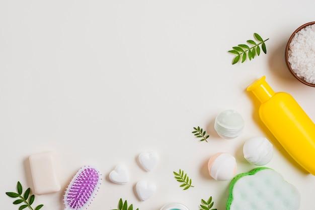 Bomba de baño jabón en forma de corazón; sal y cepillo para el pelo con una botella de cosméticos sobre fondo blanco