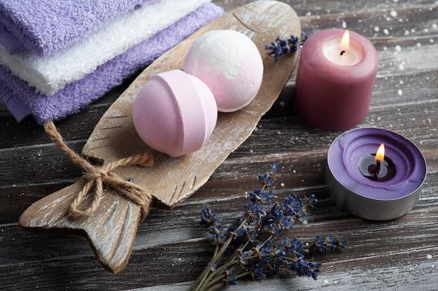 Bombas de baño de aroma de vainilla en composición de spa con flores de lavanda secas y toallas