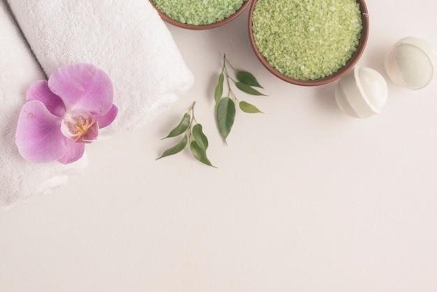 Bombas de baño, sal de mar de hierbas y toallas enrolladas con orquídea sobre fondo blanco