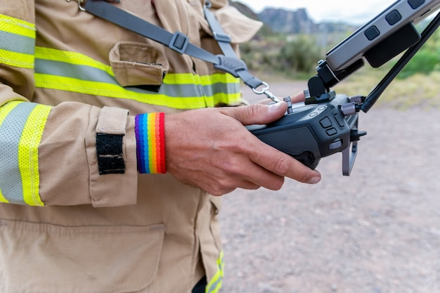 Bombero, con brazalete lgbt, operando un dron en búsqueda y rescate