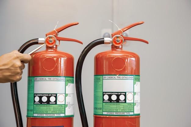 El bombero está comprobando el tanque de extintores de incendios en el edificio.