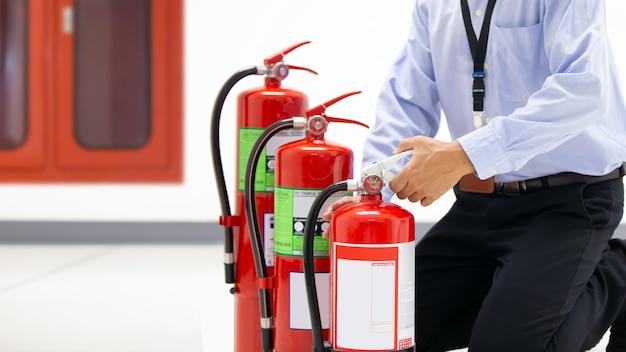 Bombero que controla la manija del extintor rojo.