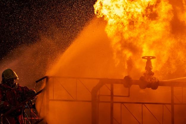 Bombero rociando la llama de la tubería