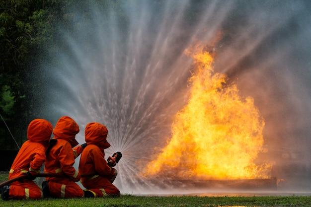 Bombero rocíe agua para disparar taller de coches en llamas entrenamiento contra incendios