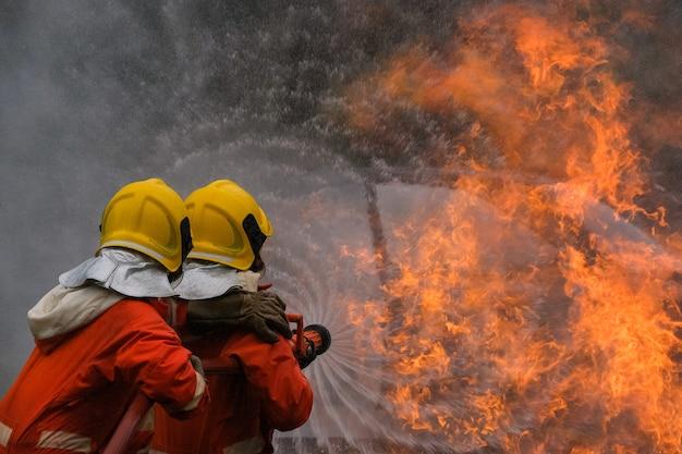 Bombero está utilizando agua en la operación de lucha contra incendios.