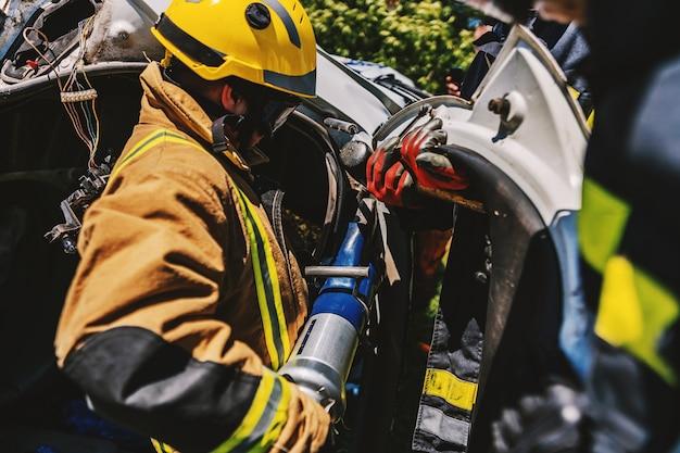 Bomberos agachados junto a un coche accidentado en llamas y tratando de voltearlo.