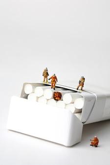 Bomberos y cigarrillos en miniatura sobre fondo blanco.