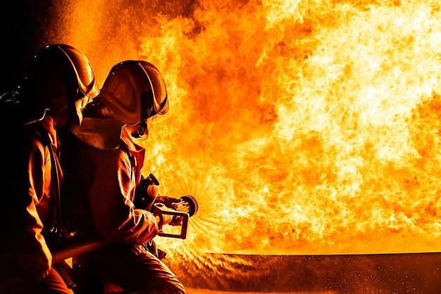 Los bomberos rociando llamas por la noche