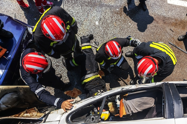 Bomberos tratando de liberar al hombre del coche accidentado. hay un coche accidentado en un accidente automovilístico.