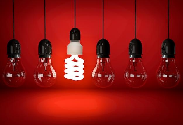 Bombilla de ahorro ecológico incandescente colgando de un cable en una fila de bombillas incandescentes sobre fondo rojo.