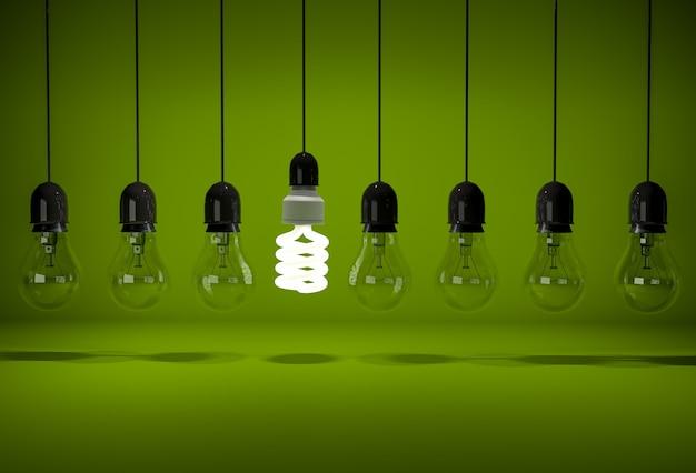Una bombilla de ahorro de energía incandescente en la fila de bombillas incandescentes oscuras colgando de cables sobre fondo verde