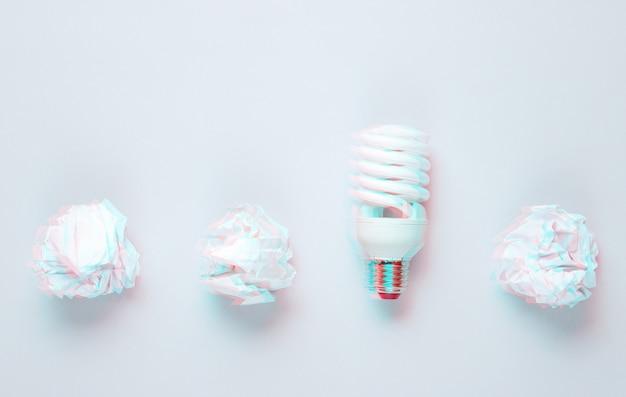 Bombilla de bajo consumo y bolas de papel arrugado sobre fondo gris. efecto de falla. vista superior