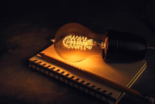 Bombilla en un cuaderno con concepto del fondo del lápiz, de la inspiración y de la educación.