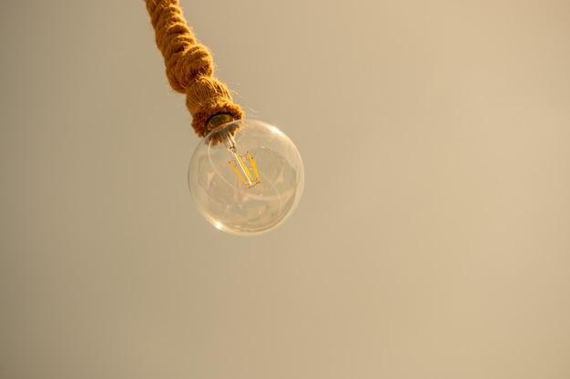La bombilla cuelga de una cuerda en un marrón pálido.