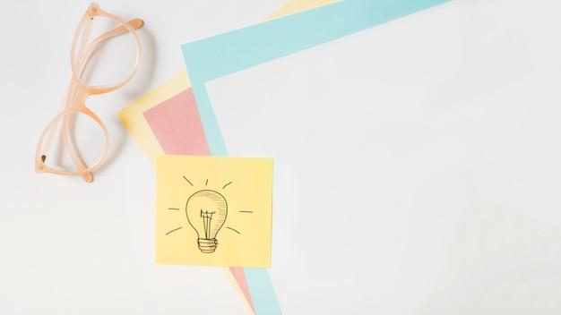 Bombilla dibujada en nota adhesiva sobre el papel de la tarjeta y anteojos sobre fondo blanco