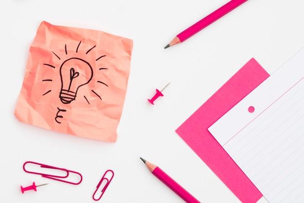 Bombilla dibujada a mano en nota adhesiva con material de oficina en fondo liso