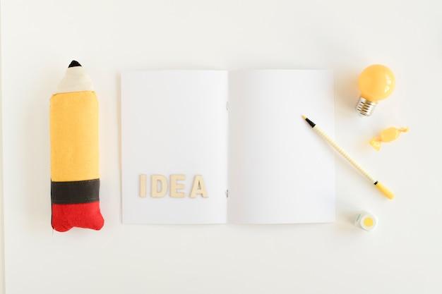 Bombilla eléctrica, caramelo, lápices con texto de idea en la tarjeta