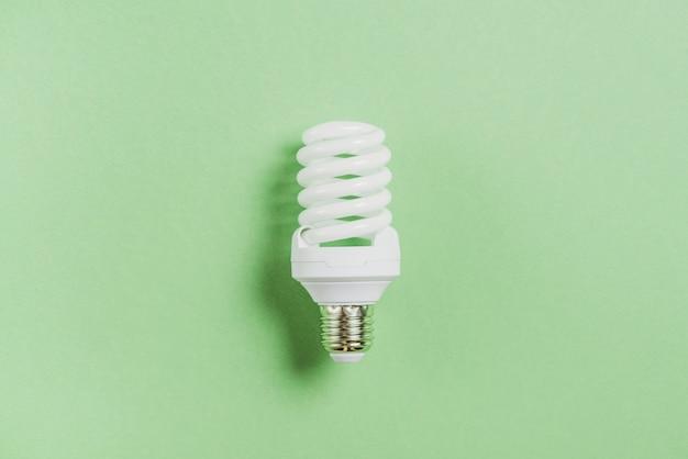 Bombilla fluorescente compacta sobre fondo verde