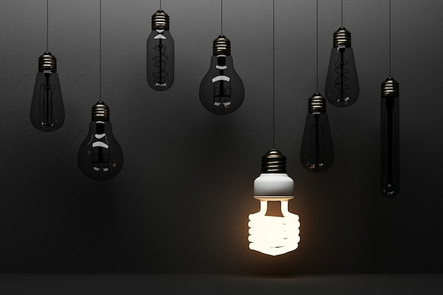 Bombilla fluorescente de luz brillante led aislado sobre fondo de hormigón negro rodeado por lámpara incandescente - representación 3d