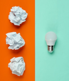 Bombilla led de bajo consumo y bolas de papel arrugado sobre fondo azul naranja. concepto de negocio minimalista, idea. vista superior