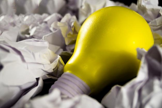 Bombilla de luz amarilla como símbolo de la idea sobre un fondo oscuro