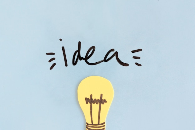 Bombilla de luz amarilla con la palabra idea sobre fondo azul