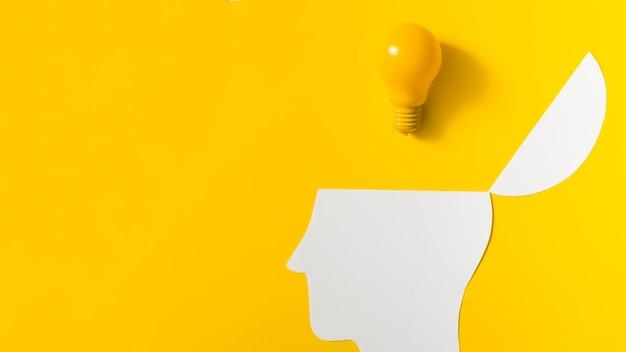 Bombilla de luz amarilla sobre el papel abierto recortar la cabeza contra el fondo de color