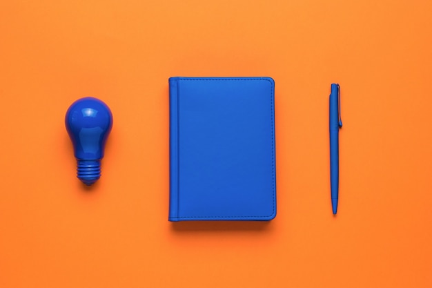 Una bombilla de luz azul, un cuaderno azul y un bolígrafo azul sobre un fondo naranja. endecha plana.
