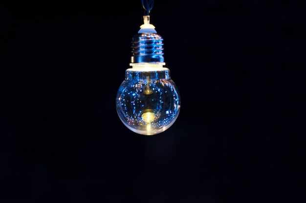 Bombilla de luz decorativa que brilla intensamente sobre un fondo oscuro