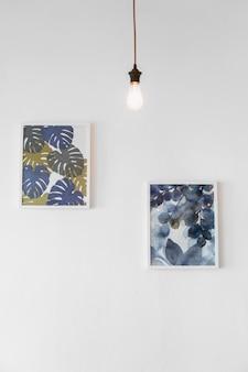 Bombilla de luz delante de la pintura en el marco de la foto adjunta en la pared blanca
