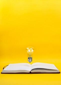 Bombilla de luz levitando sobre el cuaderno como un concepto de nueva idea, copyspace