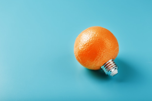 Bombilla de luz naranja sobre un fondo azul.