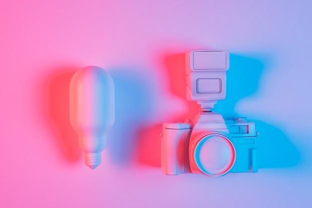 Bombilla de luz rosa y cámara con luz azul sobre superficie rosa