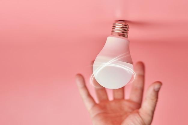 Bombilla y mano, concepto de captura de ideas. símbolo de nuevos eventos o búsqueda de soluciones a problemas. innovaciones creativas mínimas.