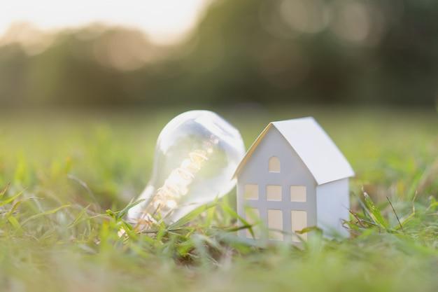 Bombilla con modelo de casa blanca en la hierba, un símbolo para la construcción,