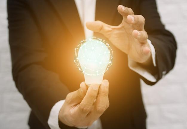 Bombilla nuevas ideas con conceptos de soluciones tecnológicas innovadoras manos del empresario.