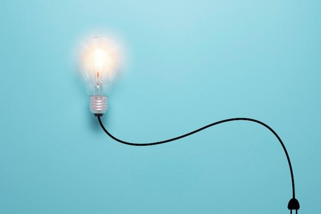 Bombilla que brilla intensamente con mazo de cables de ilustración virtual y enchufe. idea de creatividad y concepto de pensamiento inteligente.