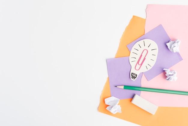 Bombilla de recorte de papel con útiles escolares sobre fondo blanco.