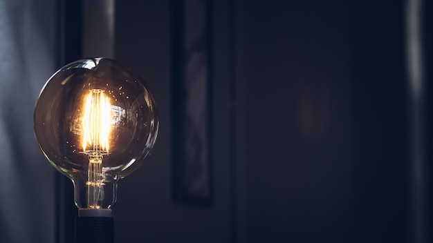 Bombilla retro sobre fondo oscuro con espacio. decoración de iluminación estilo loft macro. idea conceptual