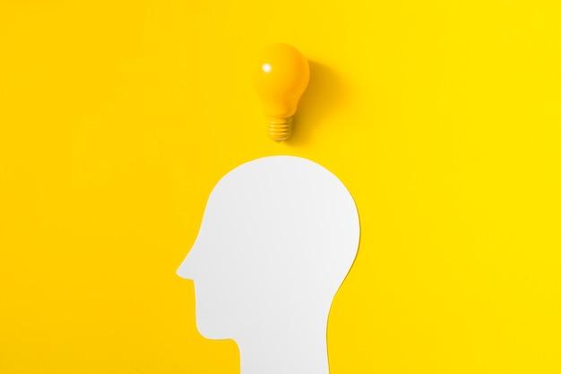 Bombilla sobre la cabeza humana blanca cortada sobre fondo amarillo